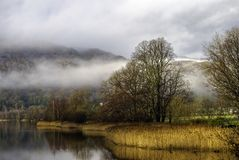 Grasmere lake. Scenic view of Grasmere lake shrouded in mist, Lake District National Park, Cumbria, England Royalty Free Stock Image