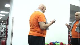 Graso coge pequeñas pesas de gimnasia en un gimnasio