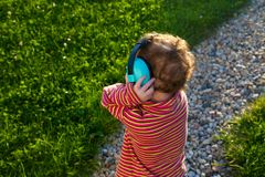 The grasp of the music. Toddler redhead girl stands on lawn at sunset with her back to the camera listening to the music with large headphones Stock Photo
