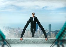 Grasping businessman holds on to a roof edge. Grasping and tenacious businessman holds on to a roof edge. Success business way concept Stock Photo