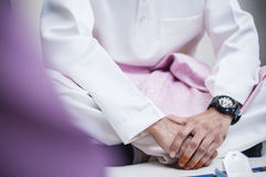 Grasping Hand. Groom grasping hand while hearing preach Royalty Free Stock Images