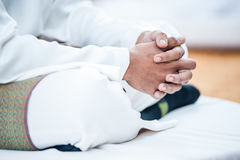 Grasping Hand. Groom grasping hand while hearing preach Stock Photo