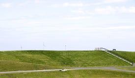 Grasrijke dijk met windturbines stock afbeelding
