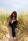 Among the grass. The girl sitting among the dunes grass Stock Photography