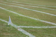 Grass athletics track showing white flag marker. Grass athletics track lanes showing white flag marker. School sports day in the summer royalty free stock photos
