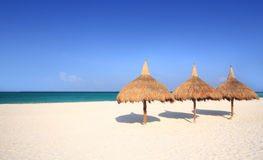 Thatch palapa umbrellas on resort beach. Thatch palapa umbrellas on a white sand resort beach. Travel & Vacation Collection stock image