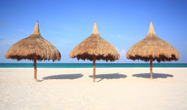 Thatch palapa umbrellas on resort beach. Three thatch palapa umbrellas on a white sand resort beach. Travel, Vacation & Hospitality Collection royalty free stock photo