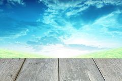 Grass and blue sky with wooden paving. Stock Image