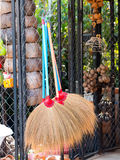 Grass broom hanging on wire fence in garden, select focus Stock Photos