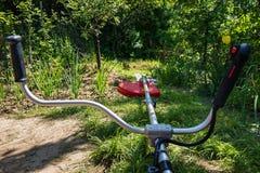 Grass cutter / brush cutter for trimming overgrown grass Stock Image