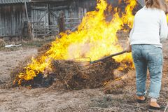 Grass is burning on the street. the fire is very big. ordinary resident trying to extinguish the fire with a pitchfork. Person firefighter safeguard emergency royalty free stock photos