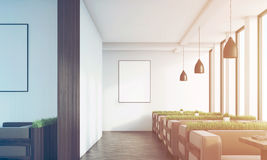 Grass cafe with posters, dark wood sofas, toned. Front view of a cafe with rows of grass and dark wood sofas standing near tall windows. Lamps above the tables Royalty Free Stock Images
