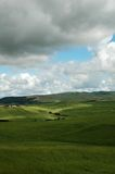 Grass and clouds. Tuscany landscape with green grass, clouds and farms on the left Royalty Free Stock Images