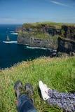 Cliffs of Moher, North Ireland sea coastline, sunny summer landscape, feet of resting people Stock Photos