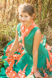 In the grass. Cute smiling girl sitting on the grass in a colored dress Stock Photo