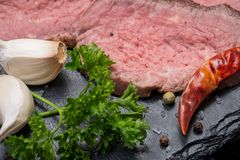 Grass Fed Corn Roast Beef garnished with Fresh Rosemary, dried Red Chile Pepper, Garlic and Rainbow  Peppercorns. On natural black stone background stock image
