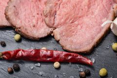 Grass Fed Corn Roast Beef garnished with Fresh Rosemary, dried Red Chile Pepper, Garlic and Rainbow  Peppercorns. On natural black stone background royalty free stock photo