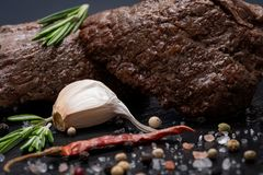 Grass Fed Corn Roast Beef garnished with Tomatoes, Fresh Rosemary, dried Red Chile Pepper, Garlic and Peppercorns. On natural black stone background royalty free stock images