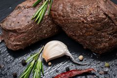 Grass Fed Corn Roast Beef garnished with Tomatoes, Fresh Rosemary, dried Red Chile Pepper, Garlic and Peppercorns. On natural black stone background royalty free stock image