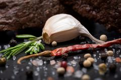 Grass Fed Corn Roast Beef garnished with Tomatoes, Fresh Rosemary, dried Red Chile Pepper, Garlic and Peppercorns. On natural black stone background royalty free stock photography