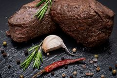 Grass Fed Corn Roast Beef garnished with Tomatoes, Fresh Rosemary, dried Red Chile Pepper, Garlic and Peppercorns. On natural black stone background royalty free stock photos