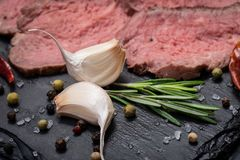 Grass Fed Corn Roast Beef garnished with Tomatoes, Fresh Rosemary, dried Red Chile Pepper, Garlic and Peppercorns. On natural black stone background stock photos