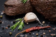 Grass Fed Corn Roast Beef garnished with Tomatoes, Fresh Rosemary, dried Red Chile Pepper, Garlic and Peppercorns. On natural black stone background stock image