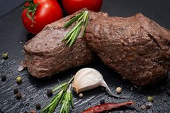 Grass Fed Corn Roast Beef garnished with Tomatoes, Fresh Rosemary, dried Red Chile Pepper, Garlic and Peppercorns. On natural black stone background stock photo