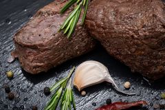 Grass Fed Corn Roast Beef garnished with Tomatoes, Fresh Rosemary, dried Red Chile Pepper, Garlic and Peppercorns. On natural black stone background stock images