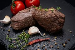 Grass Fed Corn Roast Beef garnished with Tomatoes, Fresh Thyme, dried Red Chile Pepper, Garlic and Peppercorns. On natural black stone background stock images