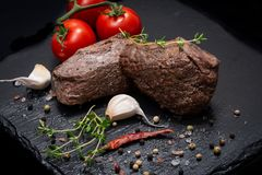 Grass Fed Corn Roast Beef garnished with Tomatoes, Fresh Thyme, dried Red Chile Pepper, Garlic and Peppercorns. On natural black stone background royalty free stock image