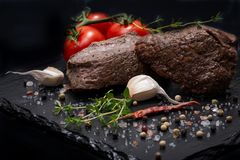 Grass Fed Corn Roast Beef garnished with Tomatoes, Fresh Thyme, dried Red Chile Pepper, Garlic and Peppercorns. On natural black stone background royalty free stock photos