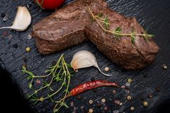 Grass Fed Corn Roast Beef garnished with Tomatoes, Fresh Thyme, dried Red Chile Pepper, Garlic and Peppercorns. On natural black stone background stock photos