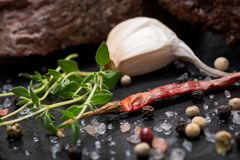 Grass Fed Corn Roast Beef garnished with Tomatoes, Fresh Thyme, dried Red Chile Pepper, Garlic and Peppercorns. On natural black stone background royalty free stock photography