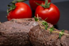 Grass Fed Corn Roast Beef garnished with Tomatoes, Fresh Thyme, dried Red Chile Pepper, Garlic and Peppercorns. On natural black stone background stock photo