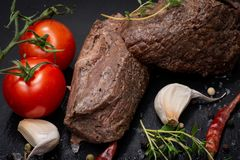 Grass Fed Corn Roast Beef garnished with Tomatoes, Fresh Thyme, dried Red Chile Pepper, Garlic and Peppercorns. On natural black stone background stock photography