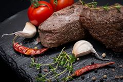 Grass Fed Corn Roast Beef garnished with Tomatoes, Fresh Thyme, dried Red Chile Pepper, Garlic and Peppercorns. On natural black stone background royalty free stock photo