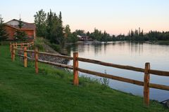 Grass, fence, and pretty river. Twilight shot of a scenic grassy area with wooden fence and a river in Fairbanks, Alaska Stock Image