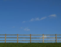 Grass Fence Sky Background. Rail fence on grass bank against blue sky with light clouds royalty free stock photo