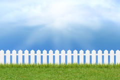 Grass and fence under blue sky and clouds. Fresh green grass and white wooden fence under blue sky ,clouds and sunlight of summer background Royalty Free Stock Images