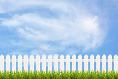 Grass and fence under blue sky and clouds. Fresh green grass and white wooden fence under blue sky ,clouds and sunlight of summer background Royalty Free Stock Photo