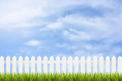 Grass and fence under blue sky and clouds. Fresh green grass and white wooden fence under blue sky ,clouds and sunlight of summer background Stock Photos