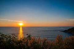 Grass Field in front of the sunset at Leam PromThep Cape in Phuket Royalty Free Stock Image
