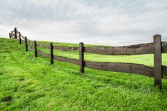 Grass field with wooden fence stock image