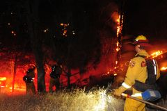 A grass fire burns as firefighters strategize. royalty free stock photos