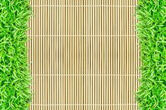 Grass frame on bamboo background Royalty Free Stock Photo