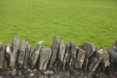 The grass is always greener. Dry stone wall with green grass on the other side, rural scene of the countryside, background image Royalty Free Stock Photography