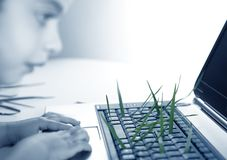Grass growing from computer keyboard, girl Stock Images