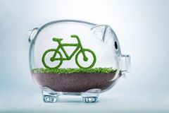 Grass eco bicycle investment concept. Grass growing in the shape of a bicycle, inside a transparent piggy bank, symbolising the need to invest in nature and a Stock Photo