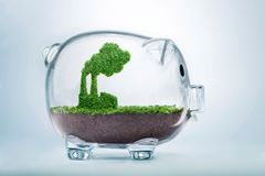 Growing eco industry fund concept. Grass growing in the shape of a factory, inside a transparent piggy bank, symbolising the need to invest in the protection of Royalty Free Stock Photo
